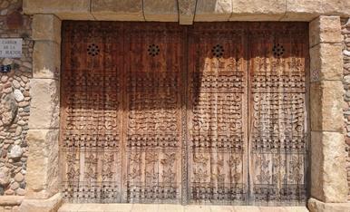 Façana de pedra amb una porta preciosa de fusta tallada a l'Espluga de Francolí