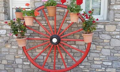 La roda de un carro antic,Combertit amb flors de primavera.