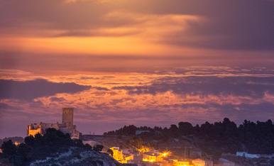 La Lluna amagada damunt el castell de Ciutadilla, dona llum als núvols del voltant