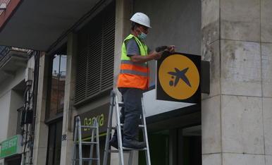 Un operari col·locant el logotip de CaixaBank a l'oficina situada al número 116 de la Rambla del Poblenou de Barcelona, anteriorment una oficina de Bankia.