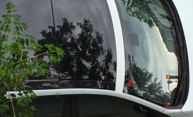 Foto artistica dels reflexos de primavera, de les fulles dels abres, en el vidre d'un cotxe