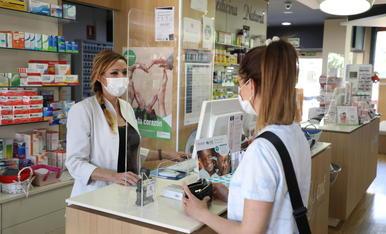 Una ciutadana compra en una farmàcia de Lleida.