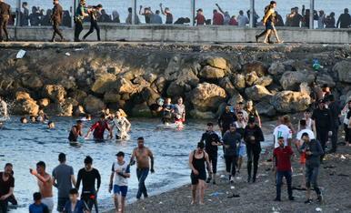 Persones migrants caminen per la platja del Tarajal, a Ceuta.
