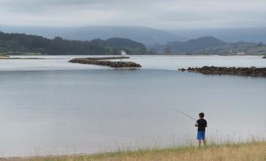 Pescando en la ría.  La ría de Villaviciosa (Asturias) es un estuario muy bien conservado y con gran valor ambiental. La foto, tomada al atardecer un día del mes de agosto, muestra la ría en las inmediaciones de la playa de Misiego, y la orografía cercana