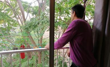 Ch. T., mirant pel balcó de casa seua, on porta cinc anys, gràcies al programa Housing First.