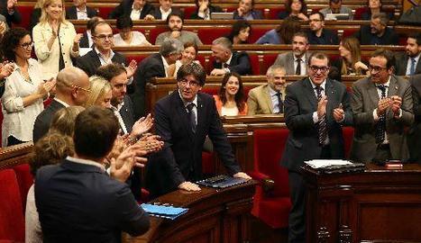 Els diputats de Junts pel Sí aplaudeixen Puigdemont després del seu discurs d'obertura mentre la resta s'estan asseguts.