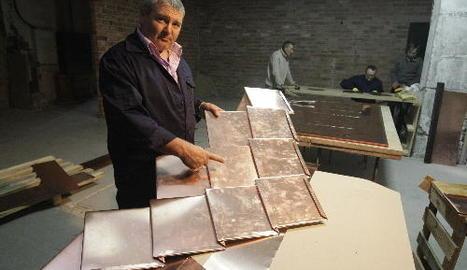 Un voluntari mostra com quedaran les llosetes de coure a les cúpules.
