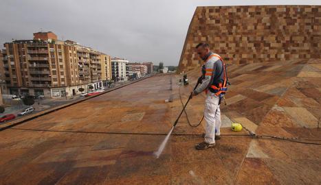 Un operari a la coberta de l'edifici netejant la pedra amb aigua a pressió.