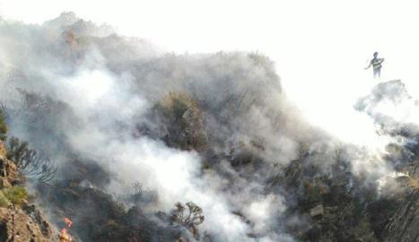 Els bombers arriben a la zona gràcies als helicòpters i treballen amb eines manuals.
