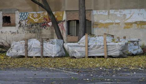 Les bigues que contenen amiant, ahir degudament protegides al pati del recinte de Magisteri.