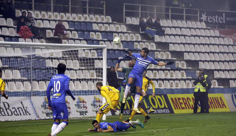 Martí salta a buscar una pilota en una acció amb el porter visitant, Moragón.
