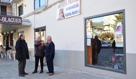 L'alcalde d'Organyà i dos veïns, ahir, sota una de les pancartes penjades al municipi per recaptar fons.