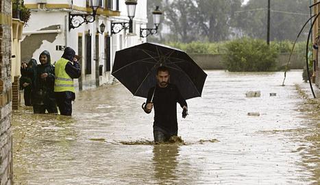 Un home camina entre les cases inundades a la barriada Doña Ana de la localitat malaguenya de Cártama per les fortes pluges.