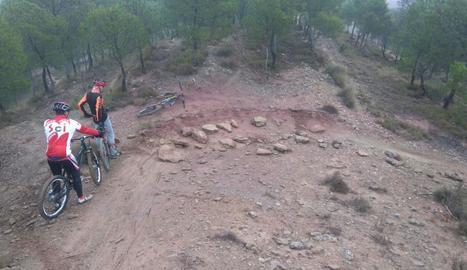 Ciclistes davant d'unes pedres que dificulten el pas.