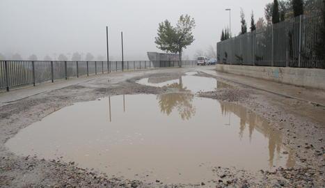 El paviment en mal estat provoca que es formin grans bassals quan plou.