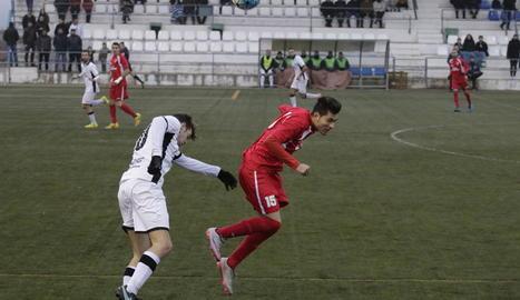 Dos oponents pugnen per una pilota aèria en una acció del partit.