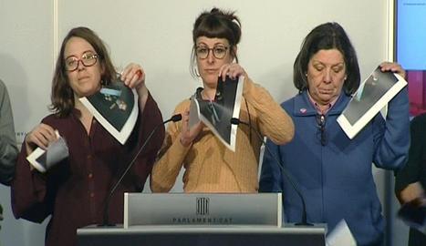 Imagen de televisión de varias diputadas de la CUP en el Parlament que rompen fotografías del Rey, durante una rueda de prensa.