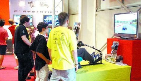 Joves jugant a un videojoc en una fira.