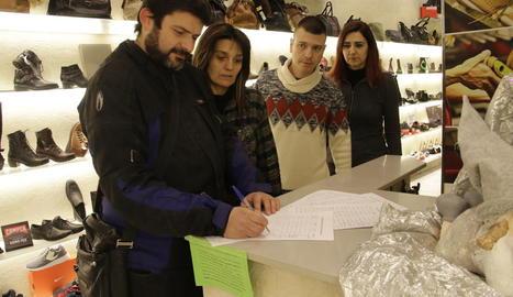 Clients firmant ahir la campanya promoguda pels comerciants.