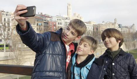 Joves es fan un 'selfie' aquest dijous amb la Seu Vella i la canalització de fons il·luminades pel sol.