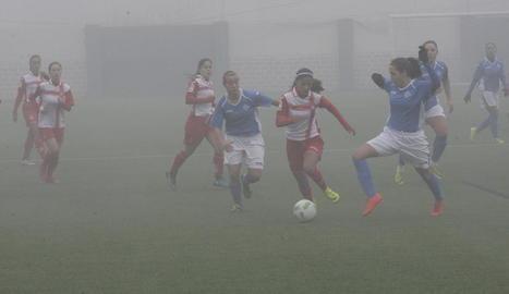 Una jugadora de l'AEM intenta frenar l'avenç d'una rival.