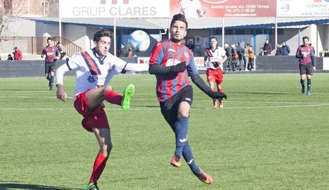 Un jugador de la UE Tàrrega intenta endur-se una pilota davant l'oposició d'un adversari.