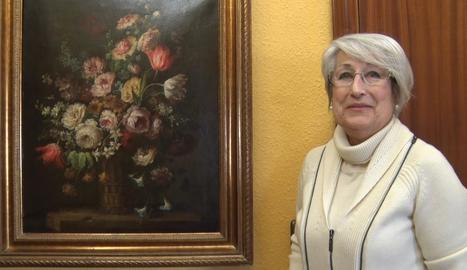 Rosa M. Martorell, de Cervera, al costat del quadre que ha recuperat del seu pare, Josep Martorell.