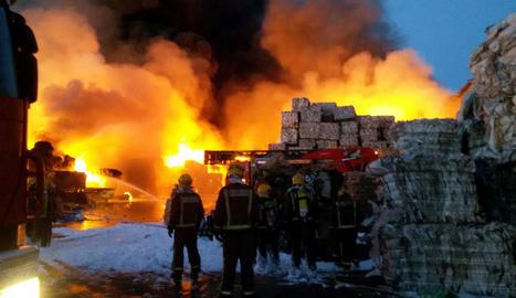 Bombers observen les flames de l'empresa de Girona.