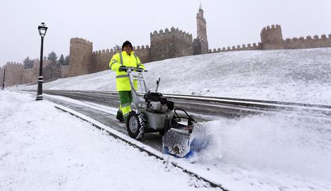 Un operari retira la neu caiguda durant la nit a Àvila.