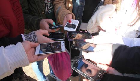 Joves mostren els seus telèfons mòbils.