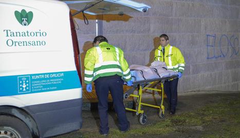 Els forenses traslladen el cadàver de la dona assassinada a Ourense.