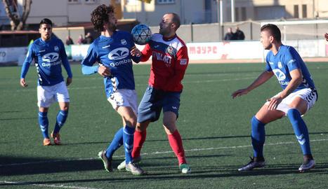 El local Adrià pugna per la pilota amb un contrari al centre del camp.
