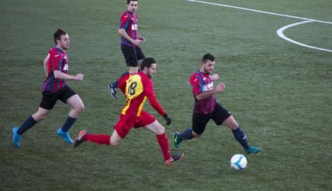 Dos jugadors pugnen pel control de la pilota en presència de l'àrbitre i d'altres futbolistes.
