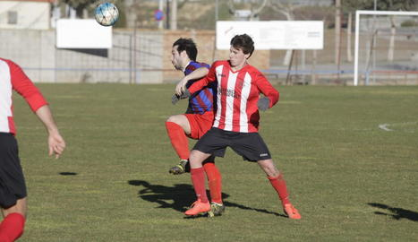 Un jugador local i un visitant lluiten per la pilota a Vilanova.