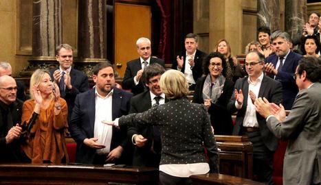 La diputada i exconsellera Irene Rigau, d'esquena, saluda el Govern mentre rep una ovació en ple del Parlament.