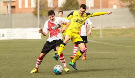 El jugador del Balaguer Sergi pugna amb un del Rubí pel control de l'esfèrica al centre del camp.