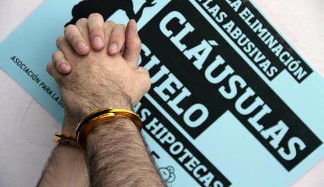 Detall de dos mans lligades durant una concentració contra les clàusules terra.