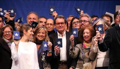 Mas mostra, amb nous associats del PDeCAT, una llibreta de la formació en la presentació del partit ahir a Barcelona.