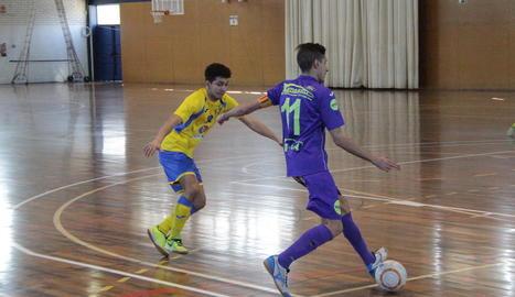 Un jugador de Lo Caragol controla la pilota davant d'un rival.