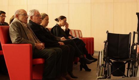 Fèlix Millet, assegut davant de la seua cadira de rodes, al costat de Jordi i Gemma Montull al banc dels acusats durant el judici.