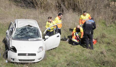 Els serveis d'emergència atenen el ferit després que el cotxe bolqués.