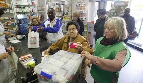 Voluntaris i una clienta solidària, a la farmàcia Isanta Crusellas.