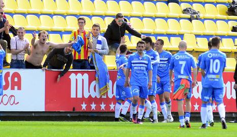 Els jugadors del Lleida celebren la victòria amb aficionats lleidatans.