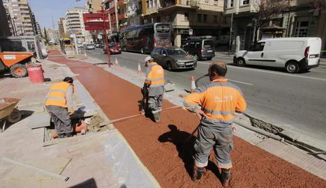 Tres operaris treballaven ahir en la col·locació del paviment del carril per a bicicletes.
