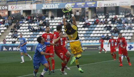 Marc Martínez, porter de l'Alcoià, bloca una pilota a servei de córner, davant d'Òscar Rubio.