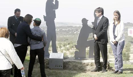 La dona i el fill d'un dels rurals assassinats, Xavier Ribes, ahir en l'acte al costat del president i la consellera Meritxell Serret.