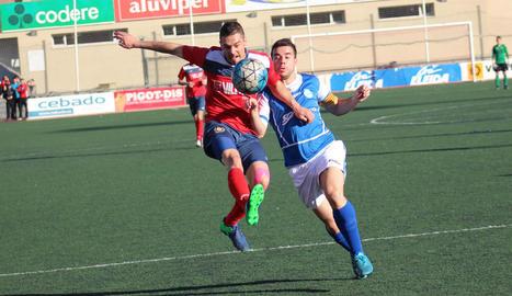 El jugador local Sergi protegeix la pilota davant la pressió d'un jugador visitant, en el partit disputat entre el Balaguer i el Morell.