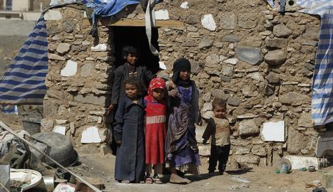 Diversos nens refugiats reunits al costat d'un refugi a Sanà.
