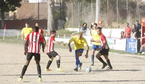 Un jugador del Castelldans intenta passar entre dos jugadors del Bell-lloc.