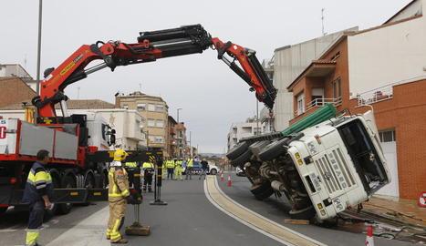 Moment en què una grua de grans dimensions remolca el camió bolcat a l'N-230, en ple centre d'Almenar.